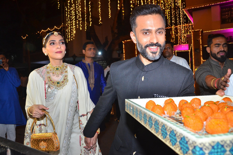 Sonam Kapoor and Anand Ahuja distributing sweetmeats