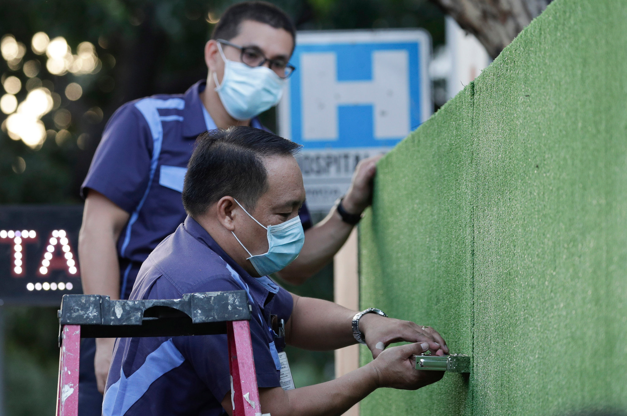 Workers set up a quarantine area for people with symptoms of the coronavirus outside a hospital in Manila