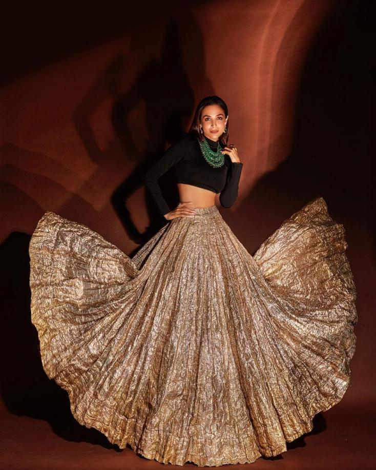 What's Diwali without a little extravagance? Malaika Arora dazzles in a gold lehenga with a plain black choli and a stunning neck piece!
