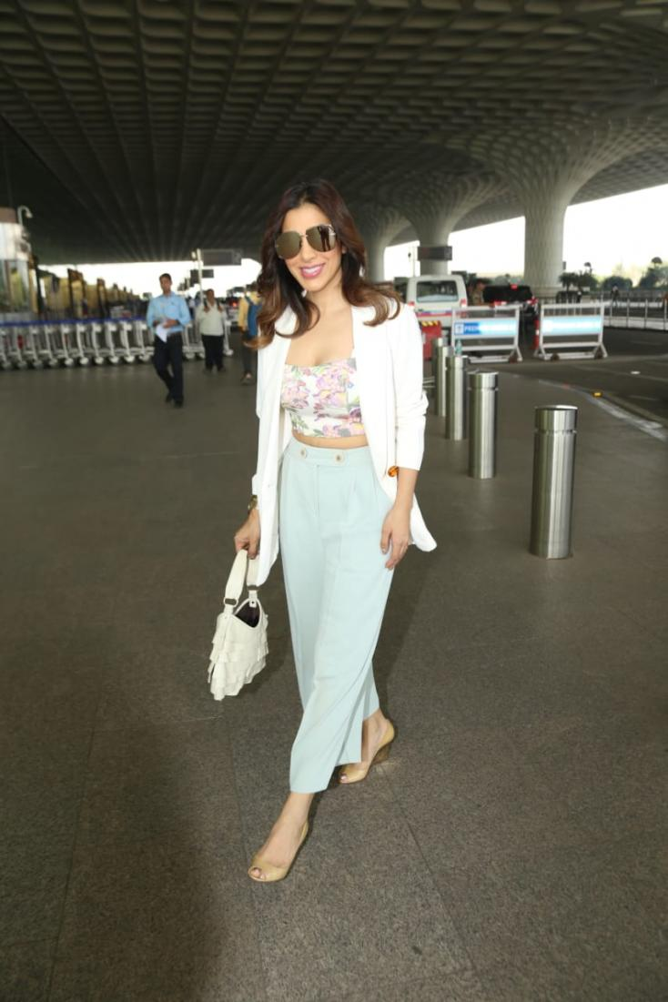 Sophie Choudry looked stunning in a printed crop top, blue pants and an overcoat as she was snapped at the airport.